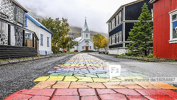 Bunter Weg inmitten einer asphaltierten Straße  der zu einer weißen Kirche führt; Seydisfjordur  östliche Region  Island