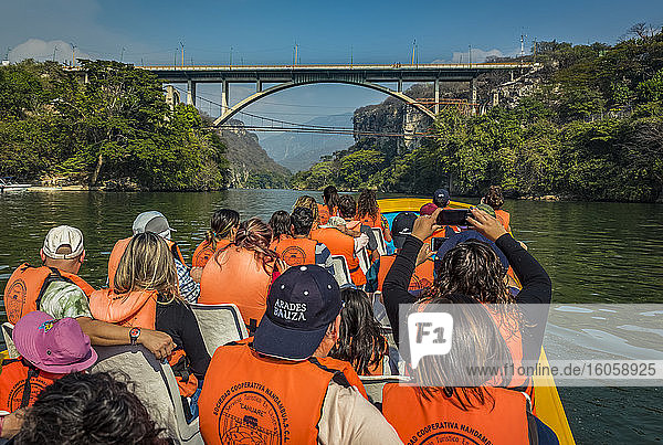 Tourists in a boat viewing Belisario Dominguez Bridge over Sumidero Canyon  Sumidero Canyon National Park; Chiapas  Mexico