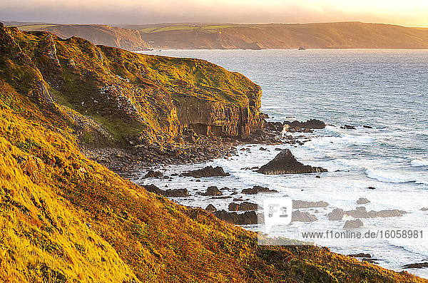 Dramatic rocky cliffs along the shoreline with the orange glow of sunset; Cornwall County  England