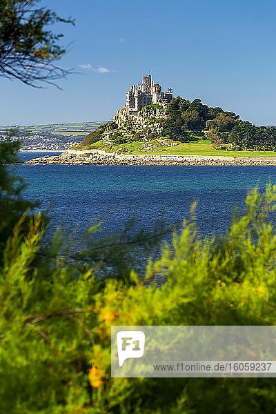 Castle of St. Michael perched on top of a rocky hill along a shoreline  surrounded by trees with blue sky  framed by foliage in the foreground; Cornwall County  England