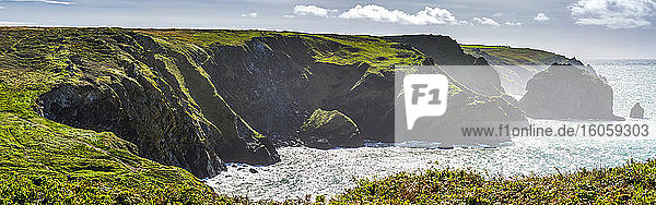 Panorama of rocky cliff shoreline with grassy fields and blue sky with clouds; Cornwall County  England