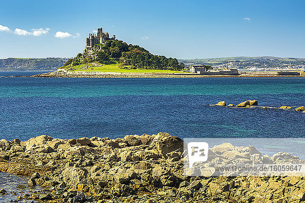 Castle of St. Michael perched on top of a rocky hill along a shoreline  surrounded by trees with blue sky; Cornwall County  England