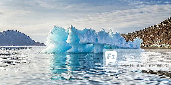 A pinnacle iceberg along the coast of Greenland in bright blue water; Sermersooq  Greenland