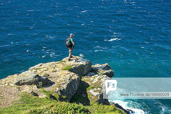 Male hiker on rocky cliff overlooking a sea of blue water; Cornwall County  England