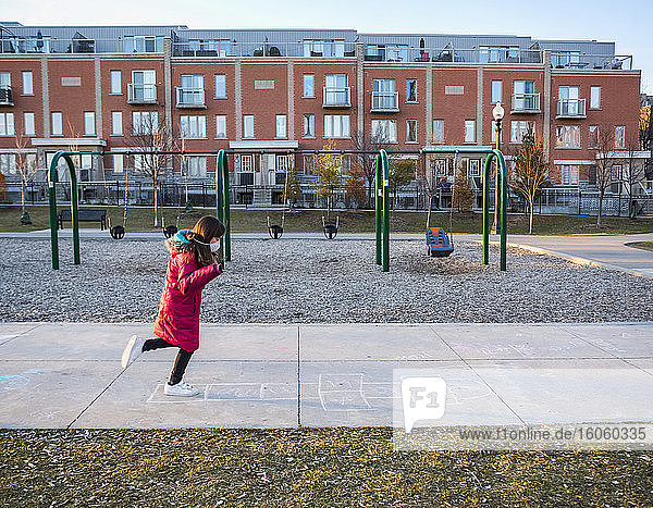 Young girl plays hopscotch at a playground and wears a protective mask to protect against COVID-19 during the Coronavirus World Pandemic; Toronto  Ontario  Canada
