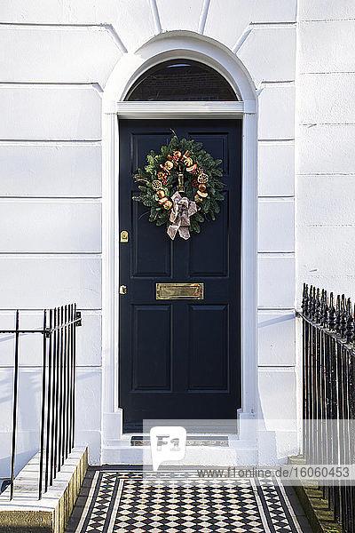 A decorative Christmas wreath on a dark blue house door; London  England