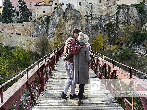 A couple walks in an embrace on San Pablo bridge; Cuenca  Castile La Mancha  Spain