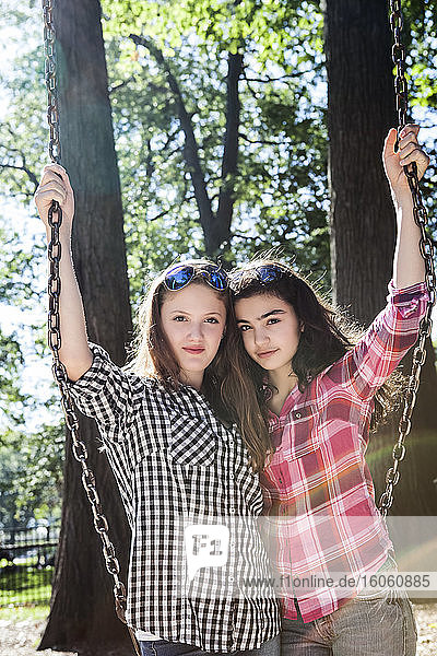 Two teenage girls posing on a swing on a playground  Woodbine Beach; Toronto  Ontario  Canada
