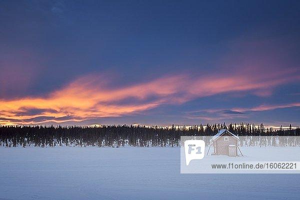 Kleine Holzhütte auf weiter schneebedeckter Ebene bei extrem tiefen Temperaturen im Morgengrauen  Skaulo  Norrbottens län  Schweden  Europa