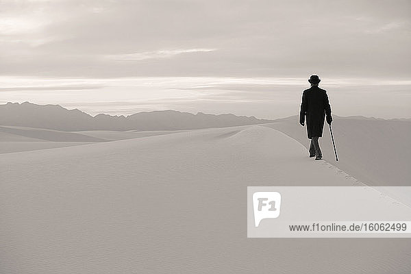 Man in a black coat and suit a bowler hat and umbrella in a white desert wilderness of white sand.