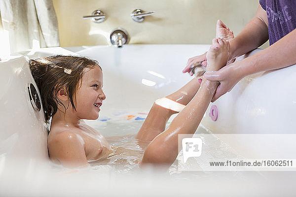 4 year old boy having a bath and shampoo in bath tub