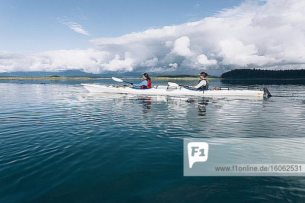 Sea kayakers paddling pristine waters of an inlet on the Alaska coastline.