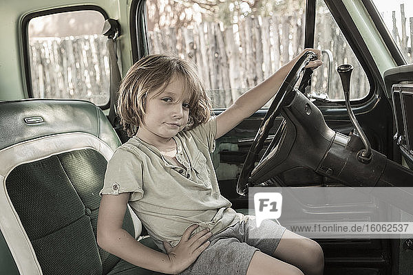 5 year old boy behind the wheel of 1970's pick up truckNM.