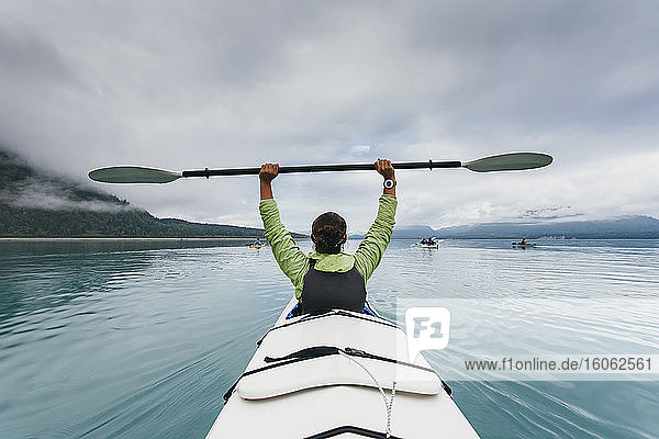 Sea kayaker extends paddle over her head pristine waters of Muir Inlet in distance Glacier Bay National Park Alaska
