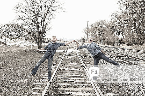 pre teen girl friends walking railroad tracks together NM.