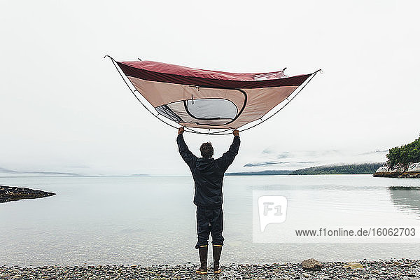 Man holding camping tent over head standing on rocky beachan inlet on the Alaska coastline.