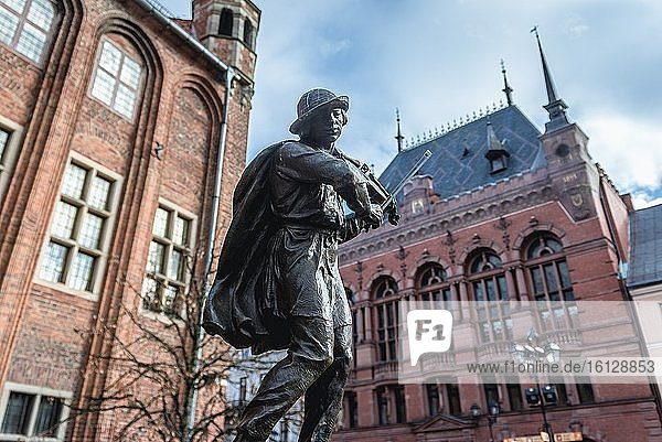 Fountain monument of Flisak - Raftsman in front of old Town Hall on Old Town of Torun  Poland  Artus Manor building on background.