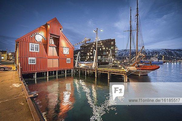 Polarmuseum am Hafen mit Spiegelung im Meer in Abenddämmerung  Polarnacht  Tromsö  Troms  Norwegen  Europa