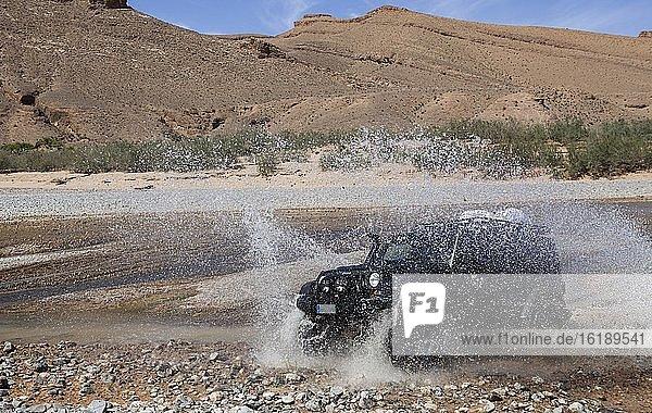 Geländewagen durchquert einen Fluss im mittleren Atlas  Marokko  Afrika