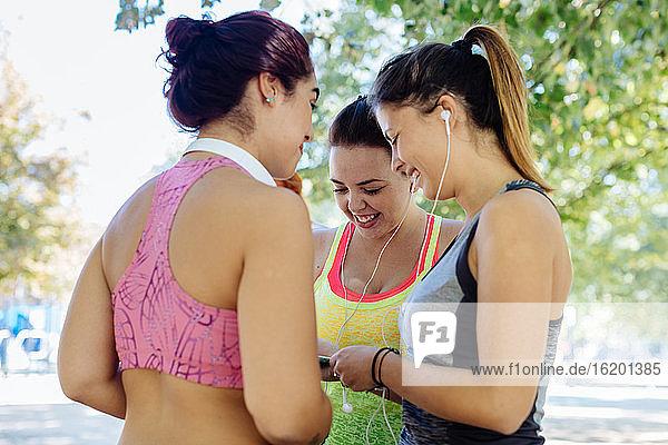 Freunde trainieren und benutzen Mobiltelefone im Park