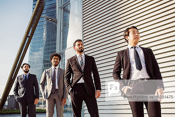 Mixed race group of businessmen hanging out together in town.