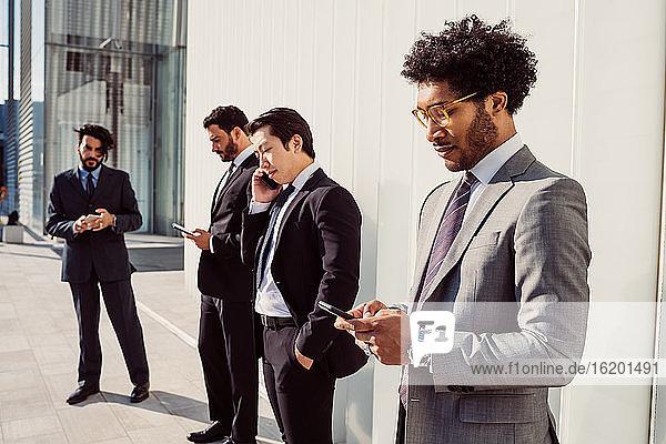 Gemischtrassige Gruppe von Geschäftsleuten  die zusammen in der Stadt herumhängen.