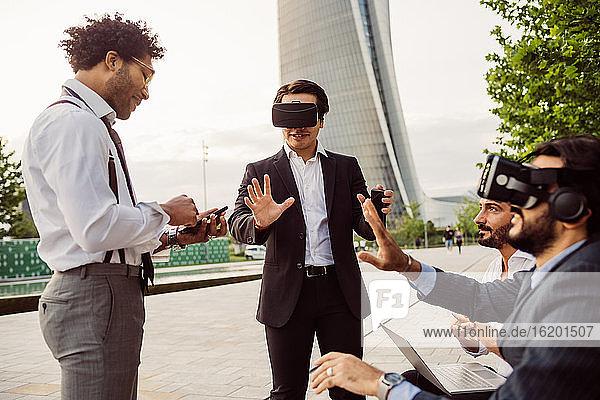 Gemischtrassige Gruppe von Geschäftsleuten  die zusammen in der Stadt herumhängen und VR-Headsets tragen.