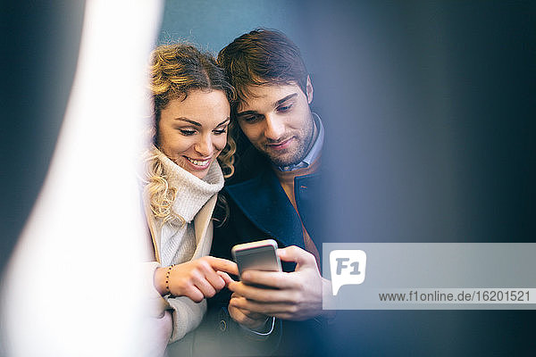Couple using smartphone inside train