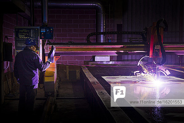 Man working in a steel factory  operating computerized welding machine.