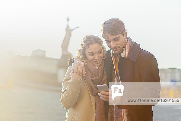 Couple using smartphone on street  Firenze  Toscana  Italy