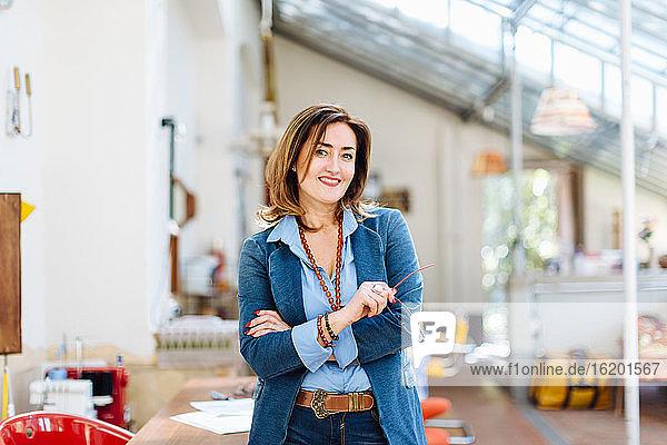 Porträt einer reifen Frau in kreativer Werkstatt  lächelnd