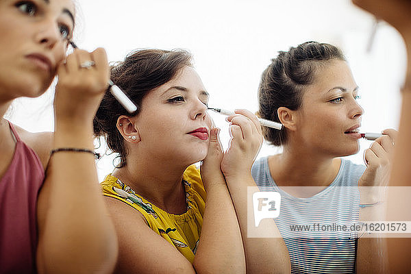 Friends putting on makeup at mirror
