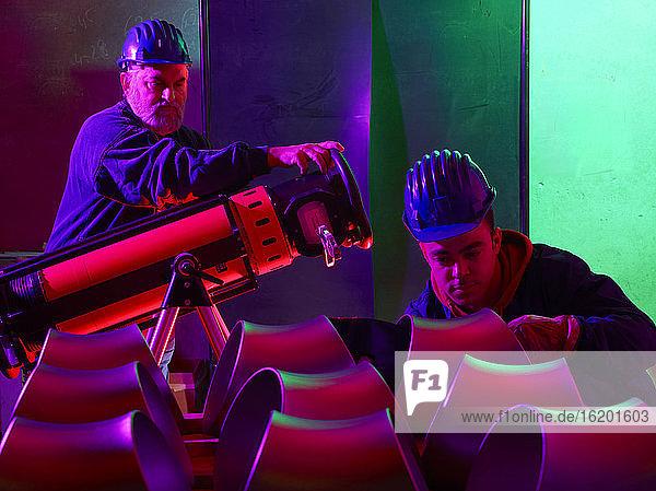 Men working in a steel factory  inspecting short steel tubes.