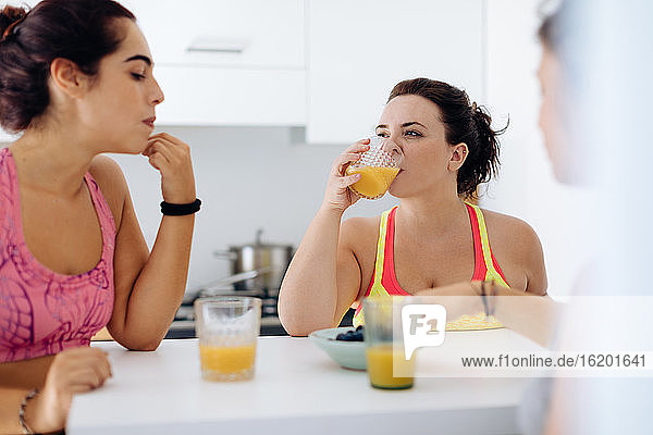 Friends enjoying juice at home after exercise
