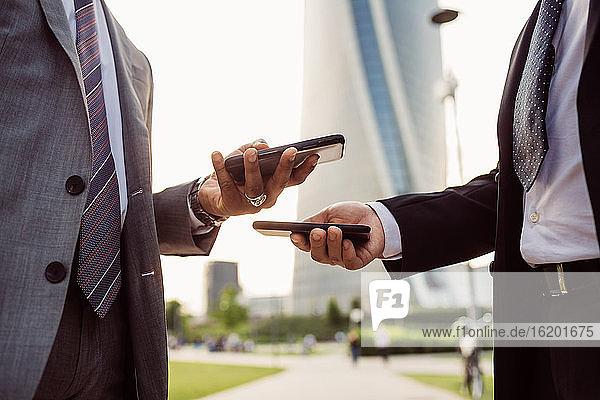 Zwei Geschäftsleute in Anzügen stehen im Freien und überprüfen ihre Mobiltelefone.