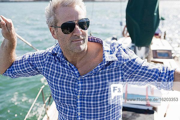 Porträt eines Mannes auf einer Jacht mit kariertem Hemd und Sonnenbrille