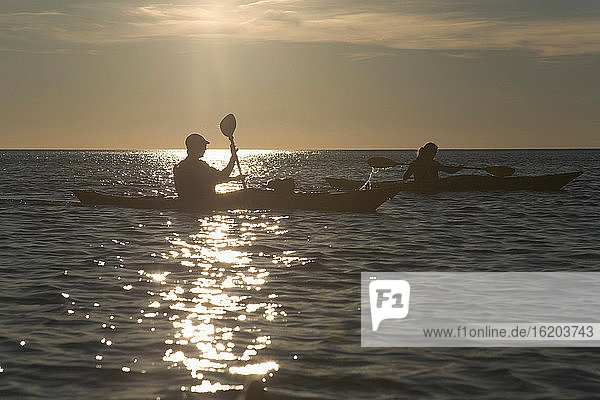 Silhouette of couple in canoes