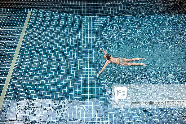 Woman swimming in pool  high angle