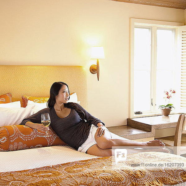 Frau liegt auf dem Bett eines Luxushotelzimmers und trinkt Wein im Napa Valley  Kalifornien