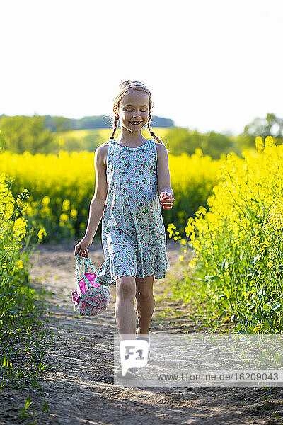 Smiling girl walking in rapeseed field