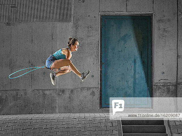 Young woman jumping over skipping rope against concrete wall under bridge