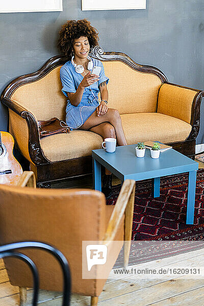 Young woman using smart phone while sitting on sofa in modern cafe