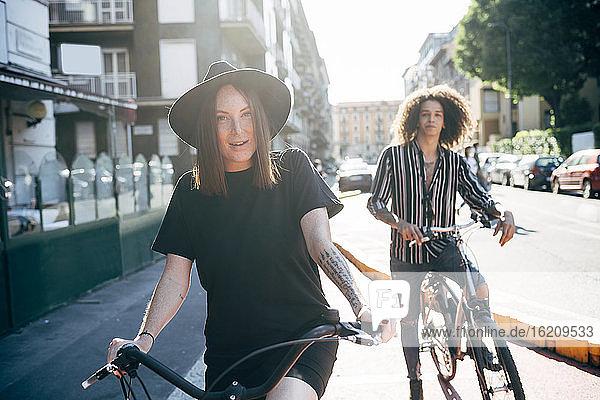 Paar auf Fahrrädern auf der Straße in der Stadt an einem sonnigen Tag