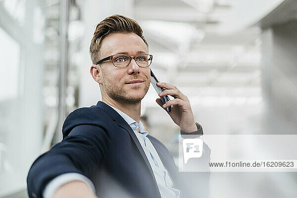Businessman wearing eyeglasses talking on phone while sitting in city