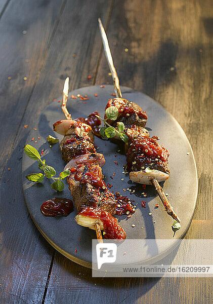 Teller mit Fleischspieß auf Holztisch  Nahaufnahme