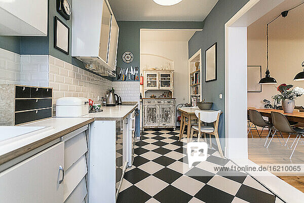 Tidy apartment kitchen with checkerboard floor