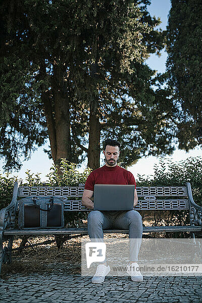 Businessman using laptop while sitting on bench in park