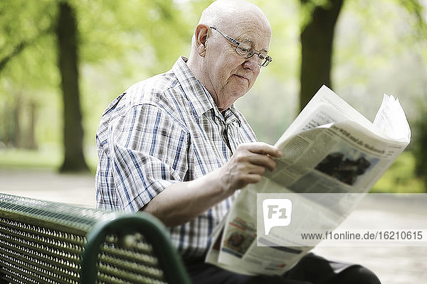 Germany  North Rhine Westphalia  Cologne  Senior man reading newspaper on bench in park
