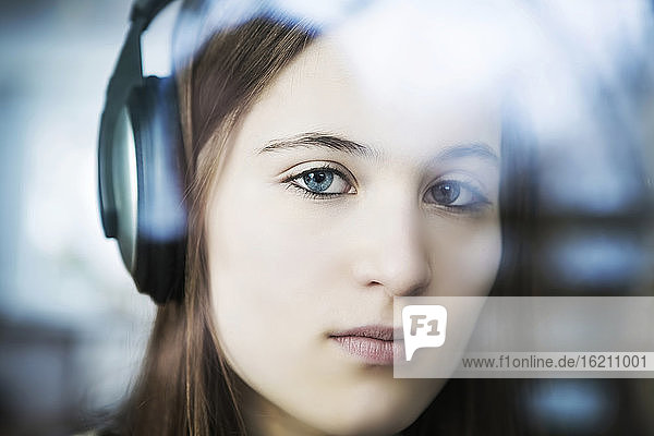 Germany  Cologne  Portrait of teenage girl listening music with headphones  close up