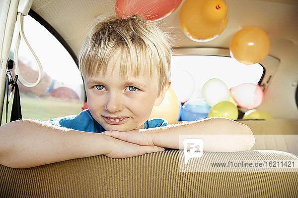 Deutschland  Nordrhein-Westfalen  Köln  Porträt eines Jungen  der sich lächelnd auf einen Autositz stützt